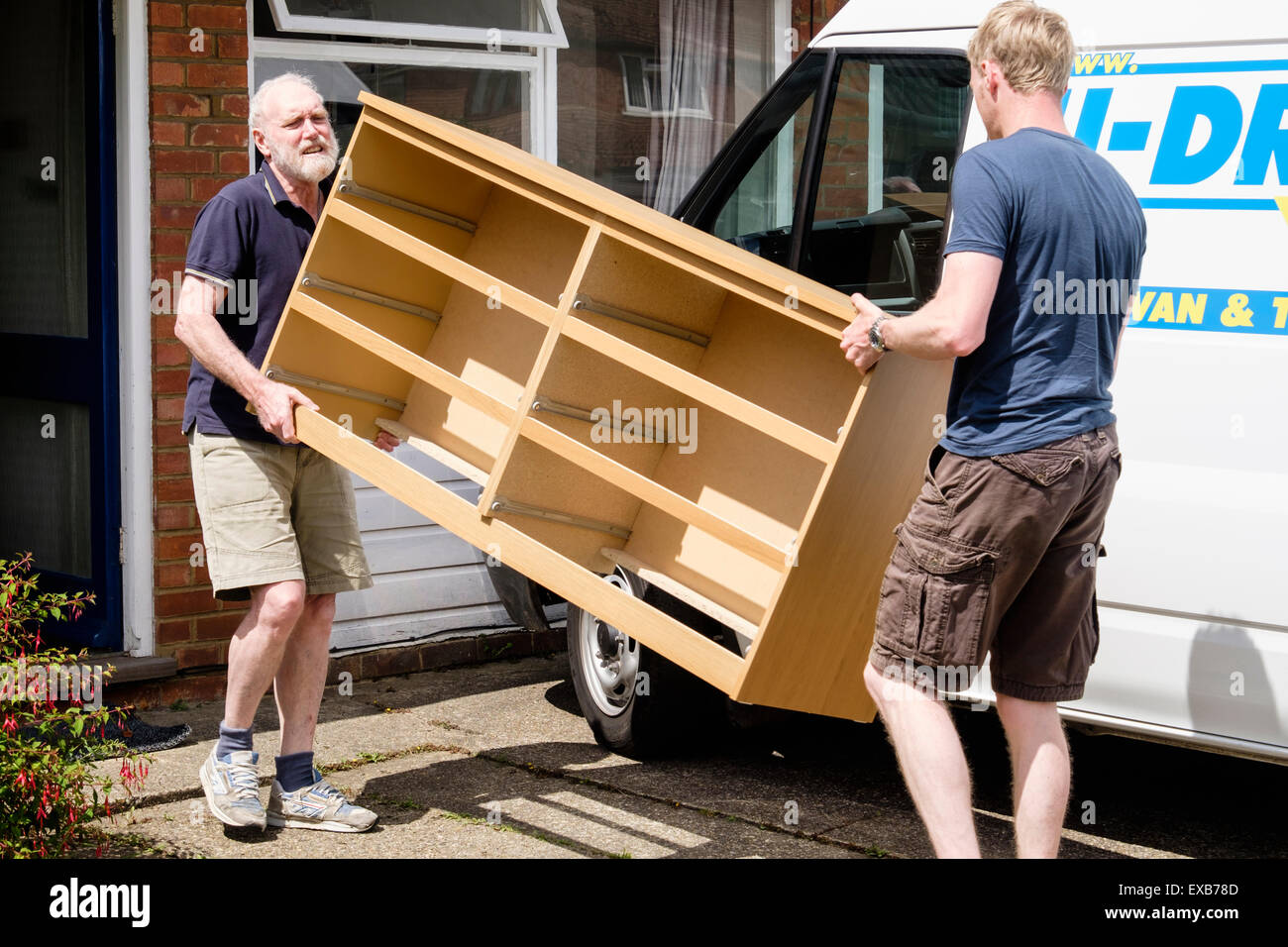 Father helping son to move furniture out of a house carrying a chest of drawers in to a self-drive hired removal Stock Photo