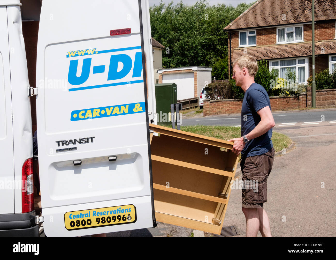 A man putting a chest of drawers furniture in to a self-drive hired removal van for house removals. Surrey, England, Stock Photo