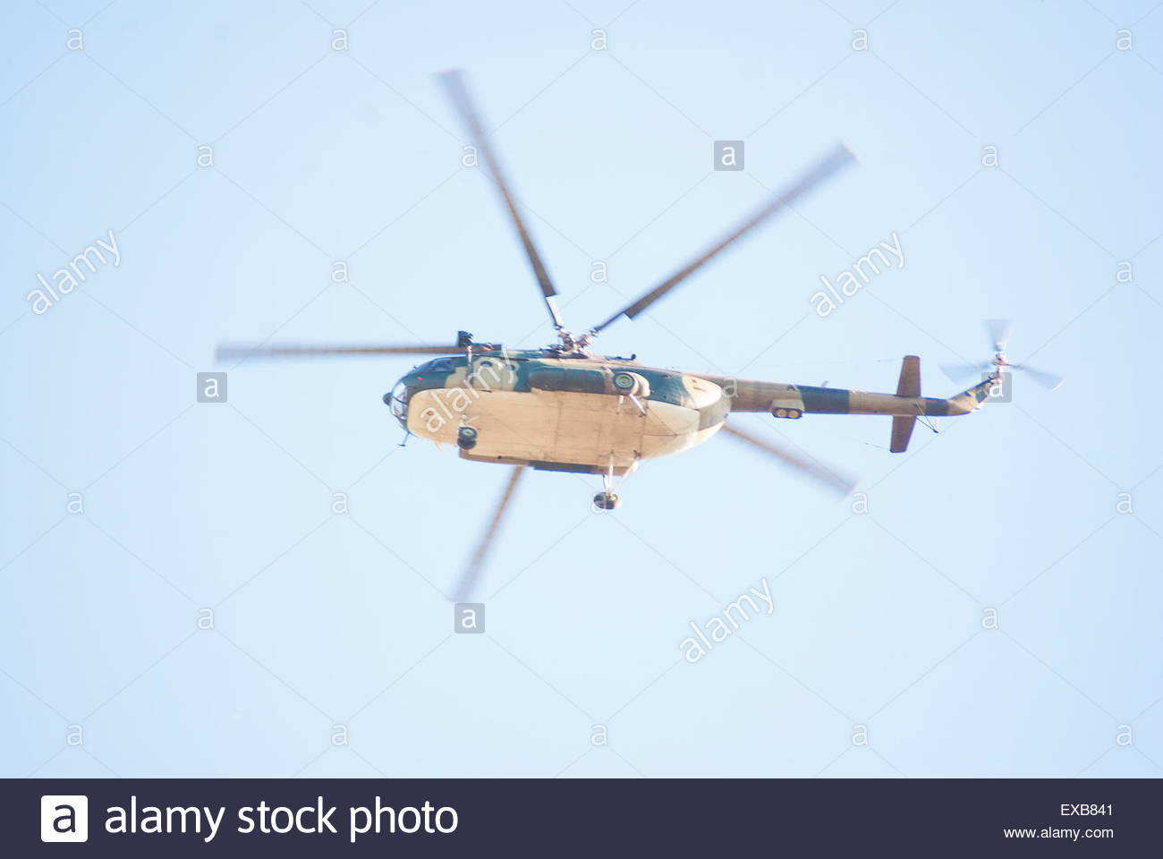 military helicopter flying at the beautiful sunny day blue sky - Stock Image