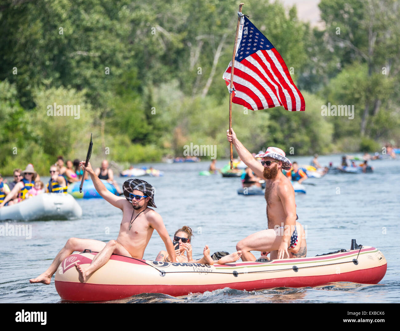 Floating the Boise River on the 4th of July. Man with USA flag, hat and swim trunks celebrating the 4th on a raft. - Stock Image