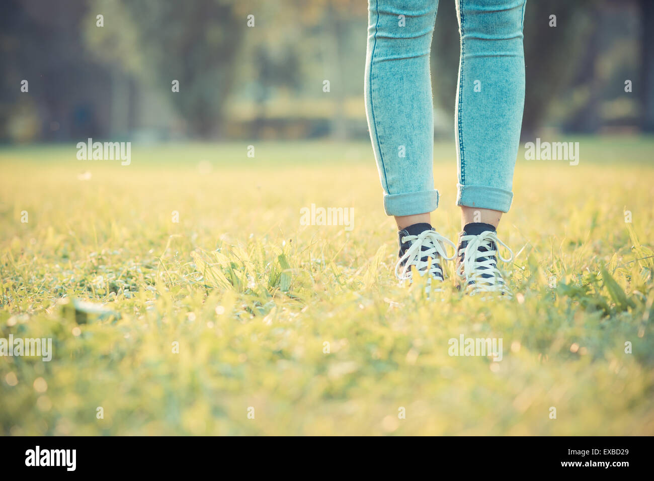 close up of legs woman with leggings and skeakers at the park on grass - Stock Image