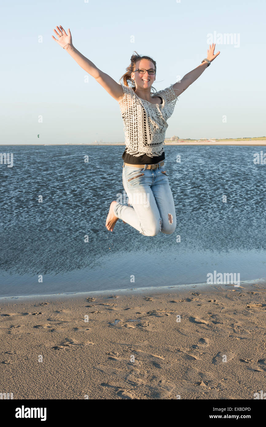 Young girl making a joy jump at sunset on the beach - Stock Image