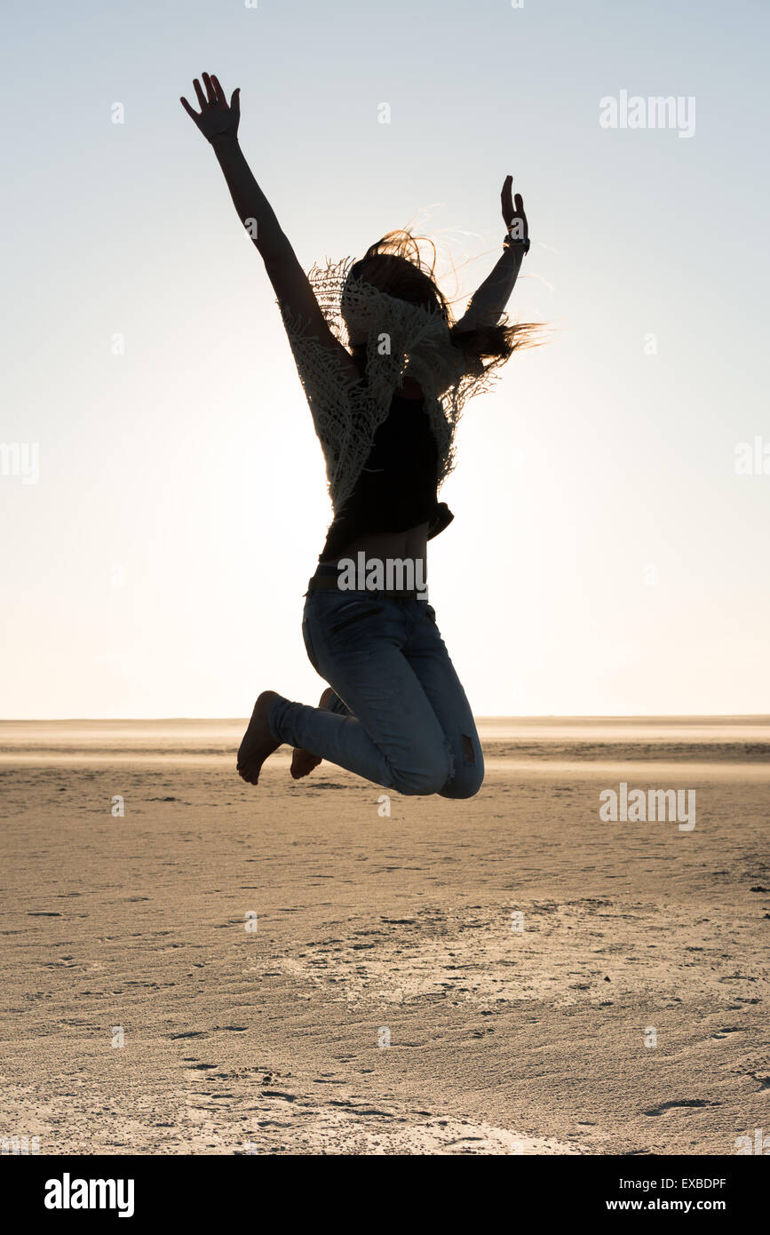 The silhouette of a girl making a joy jump at sunset on the beach - Stock Image