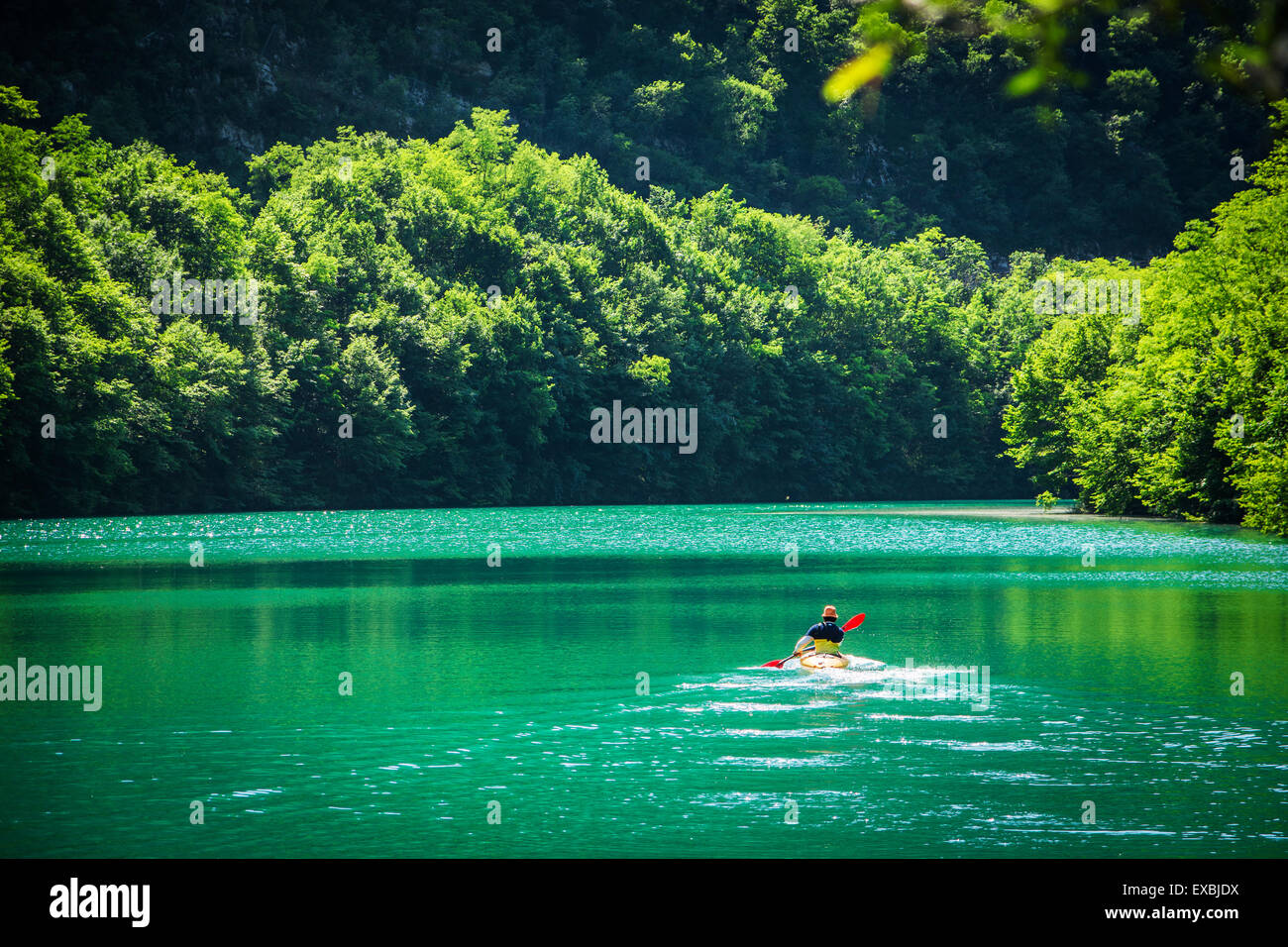 Lonely Adventurer Kayaking at the Beautiful Lake with Tranquil Panorama View. - Stock Image