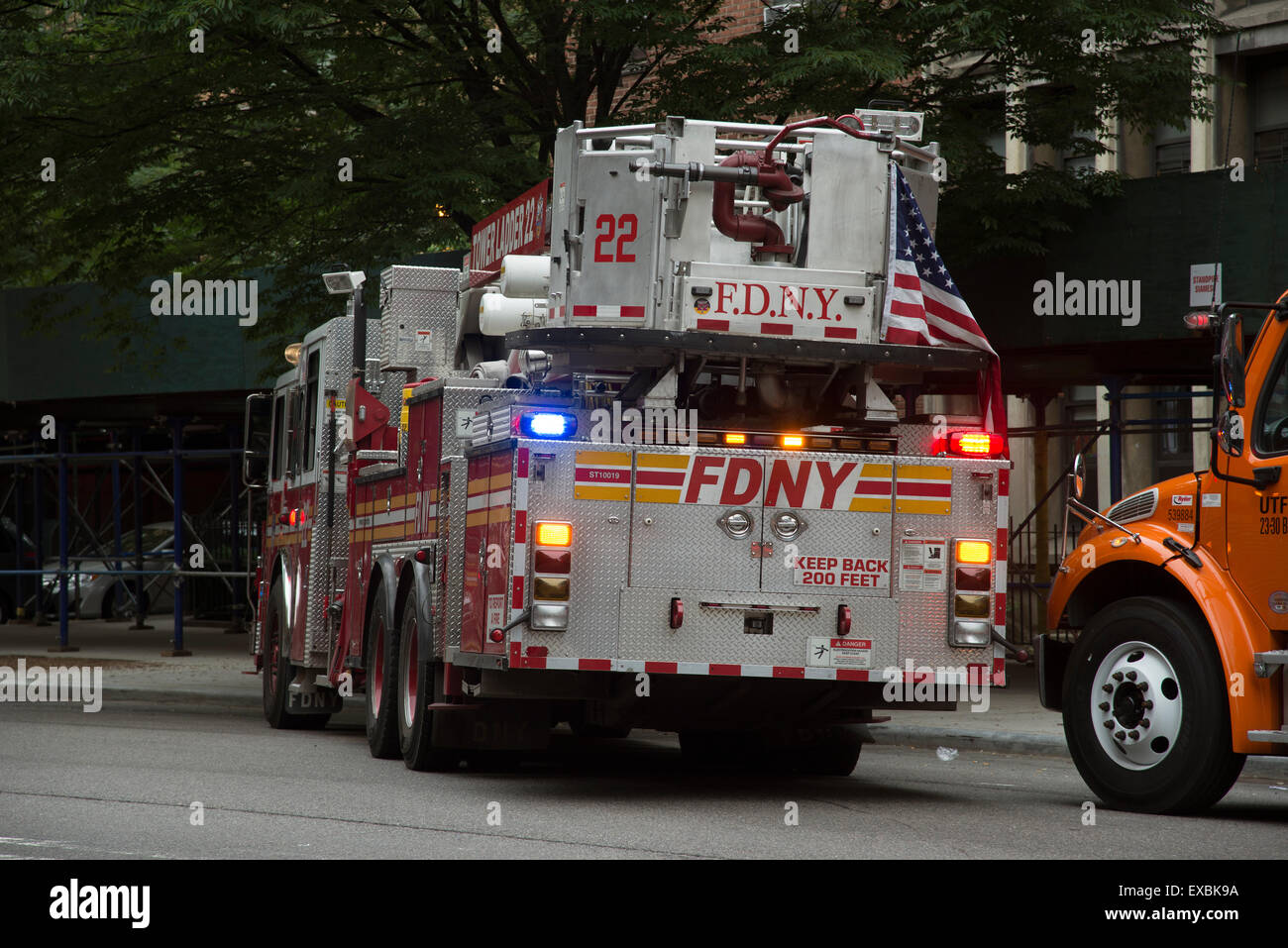 Tower ladder fire truck rear view with flag Manhattan New York USA Stock Photo