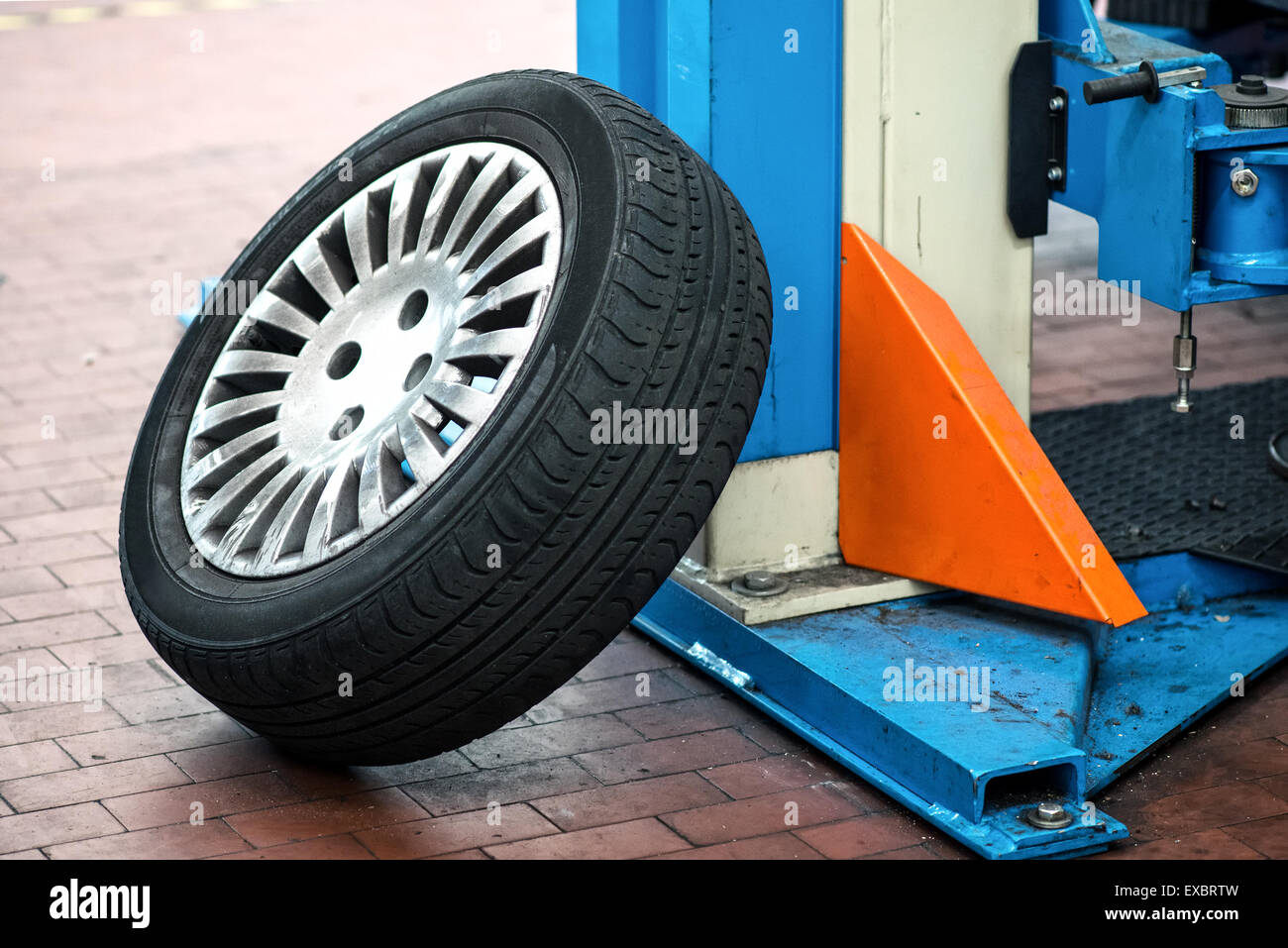Car wheel leaning up against the support of a hoist or elevator in a garage or repair workshop - Stock Image