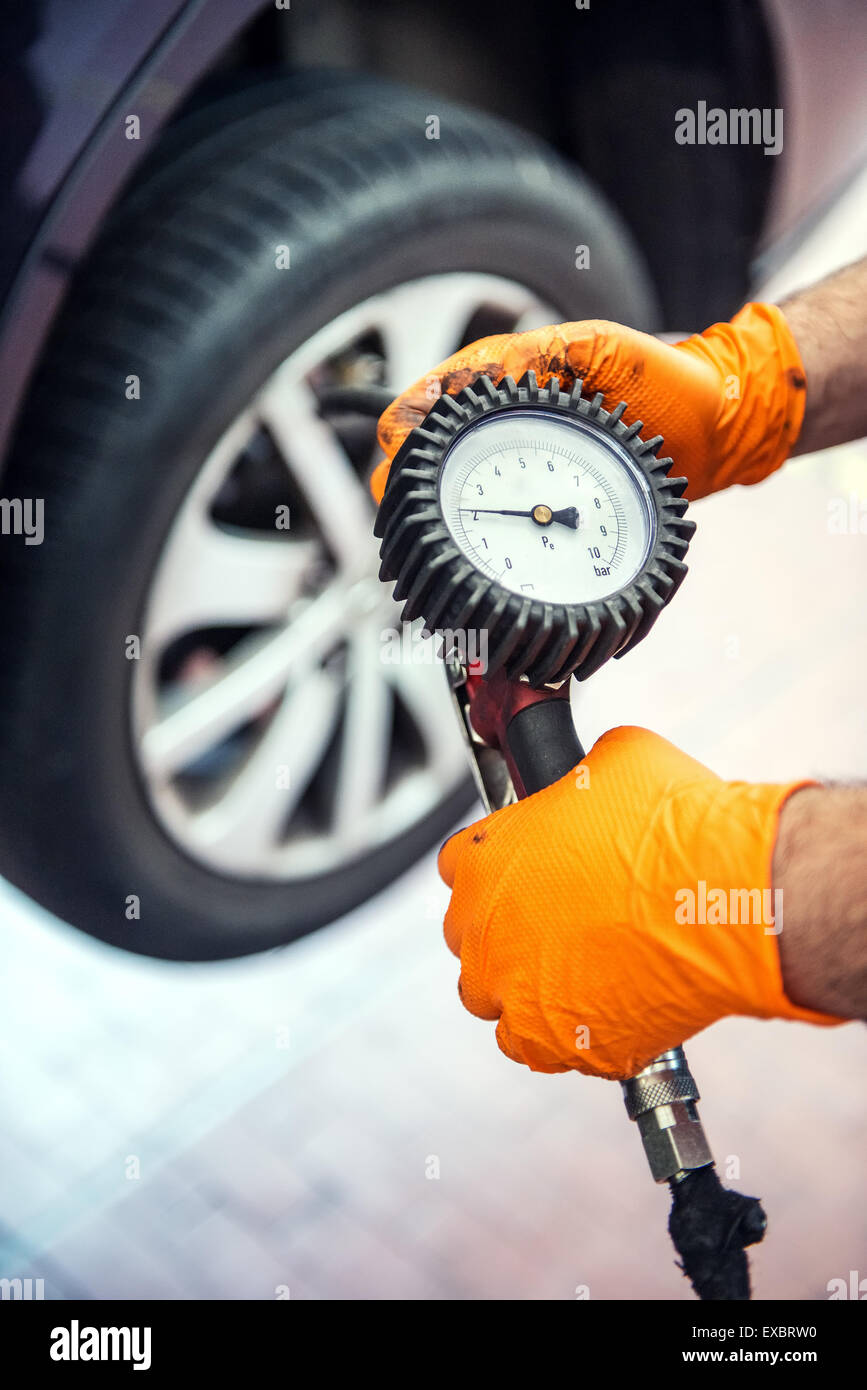 Car mechanic checking tire pressure holding a gauge attached to an air pump in his hand as he kneels alongside the - Stock Image