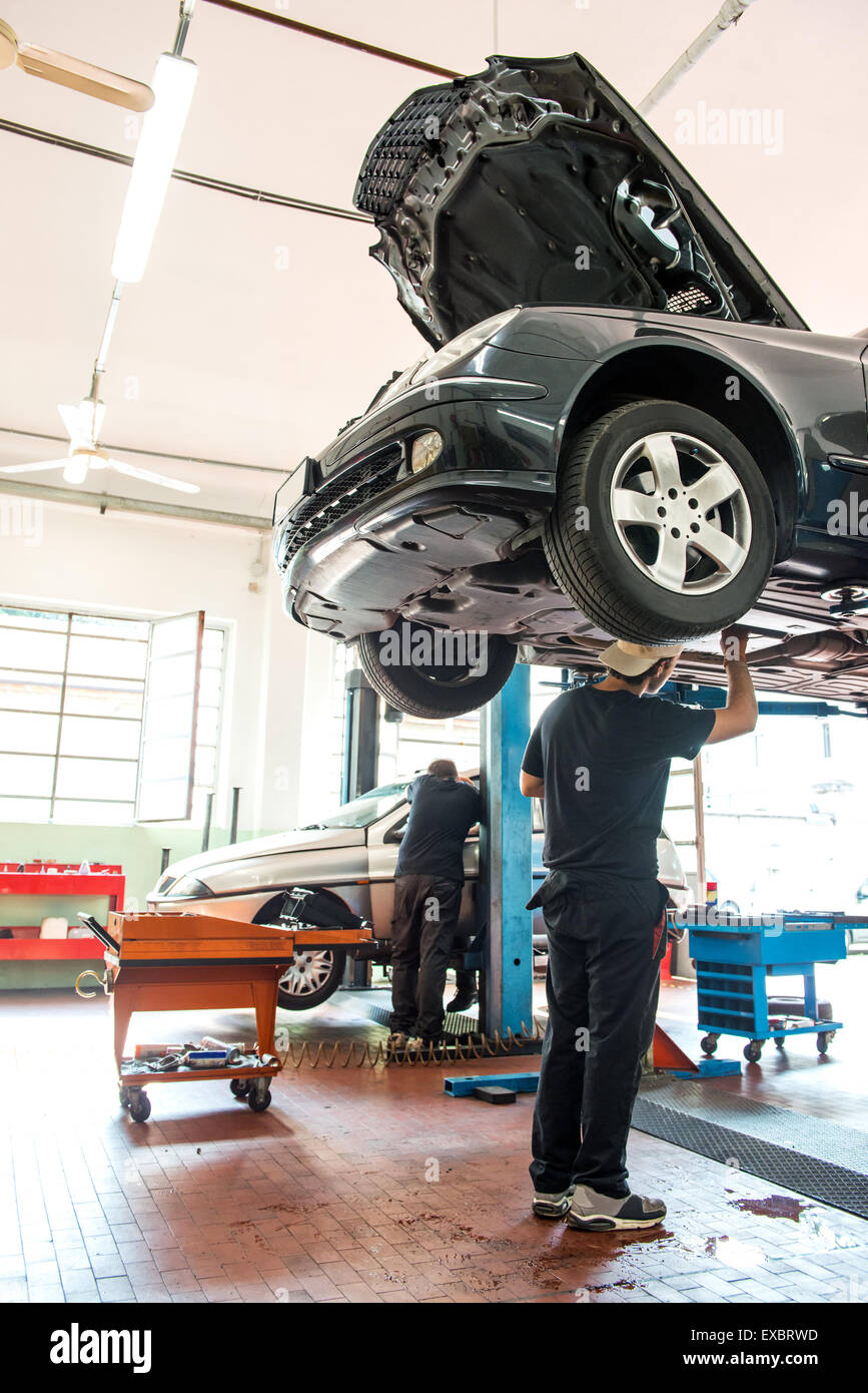 Motor mechanic working on a car on a hoist or lift in a repair workshop or garage during emergency repairs or a - Stock Image