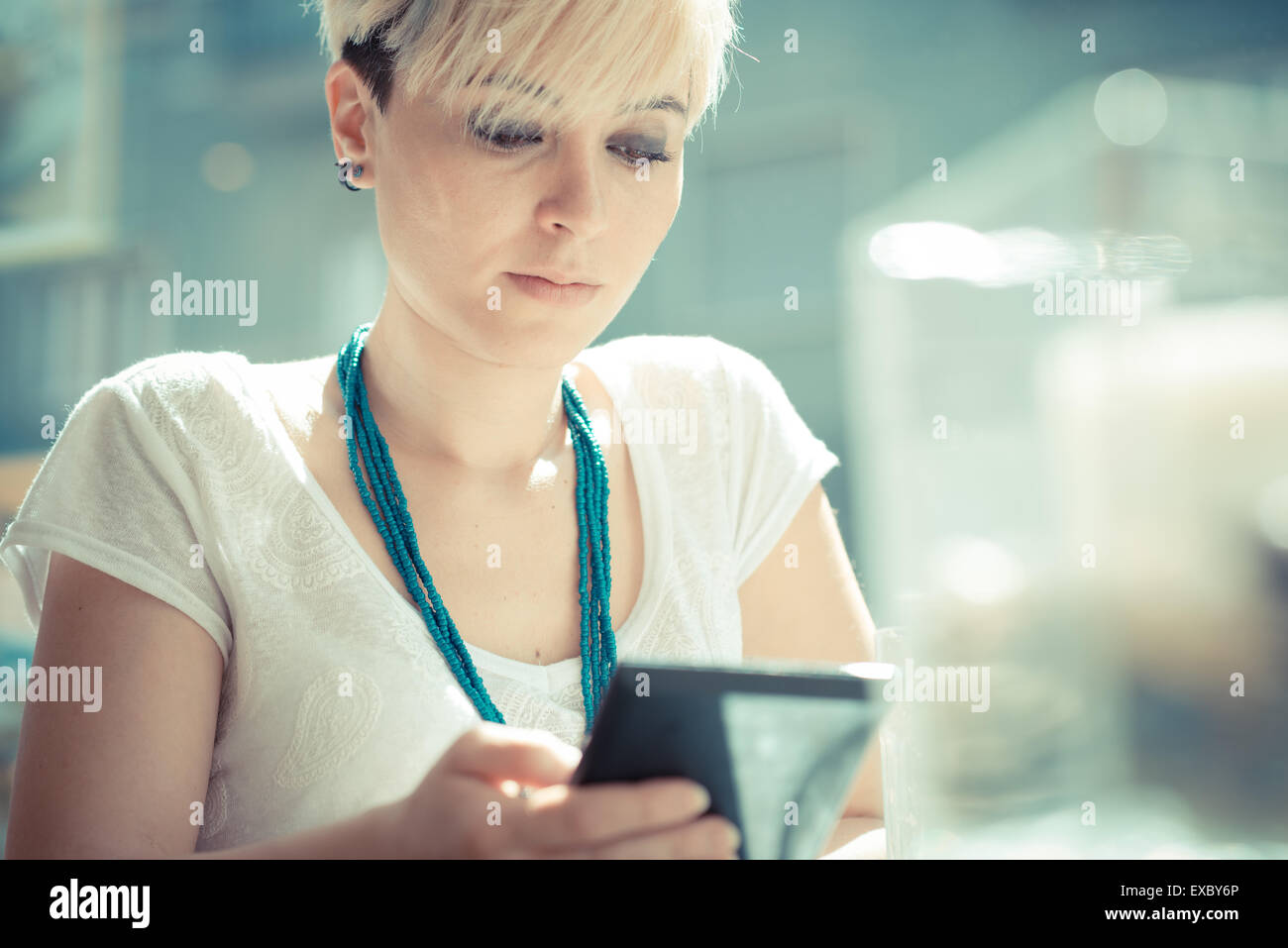 beautiful young blonde short hair hipster woman using tablet at the cafe - Stock Image