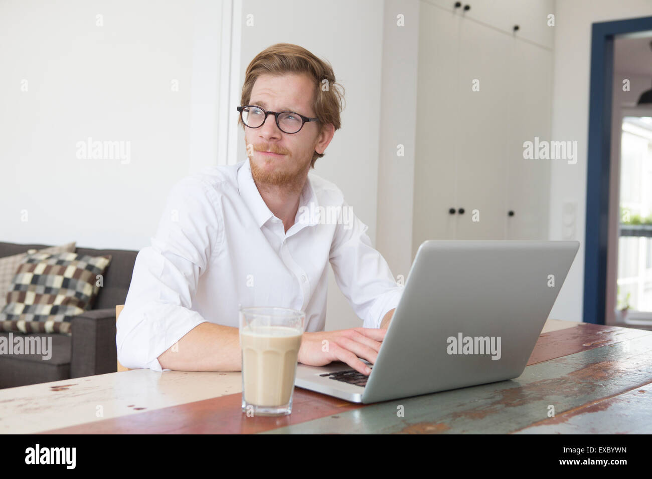red-haired young man sitting at table with his laptop and looking thoughtfully - Stock Image