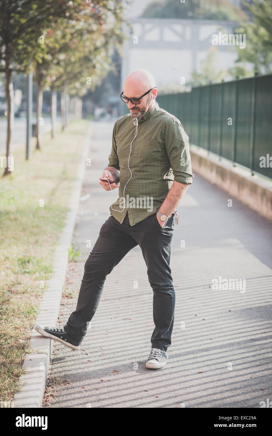 handsome middle aged man listening to music in the city - Stock Image