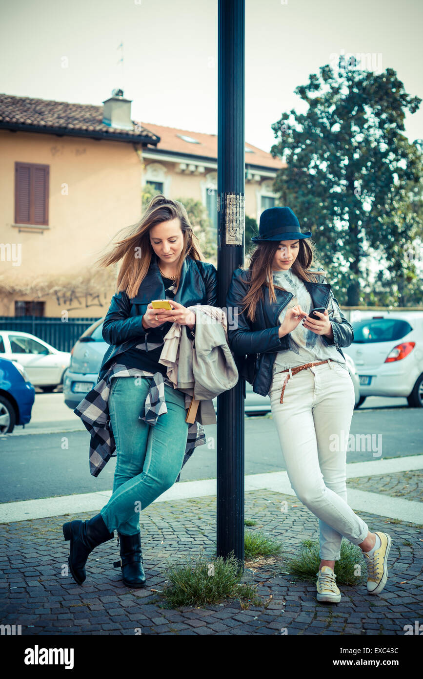 two beautiful friends authentic in urban contest - Stock Image