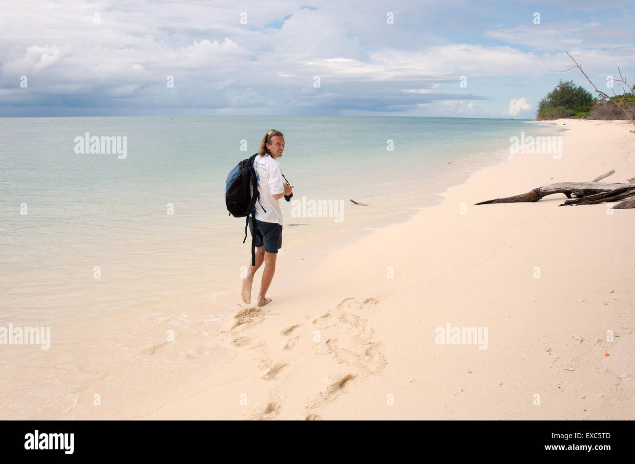 man walking along the sandy shores of the Indian Ocean, Denis island, Seychelles Stock Photo