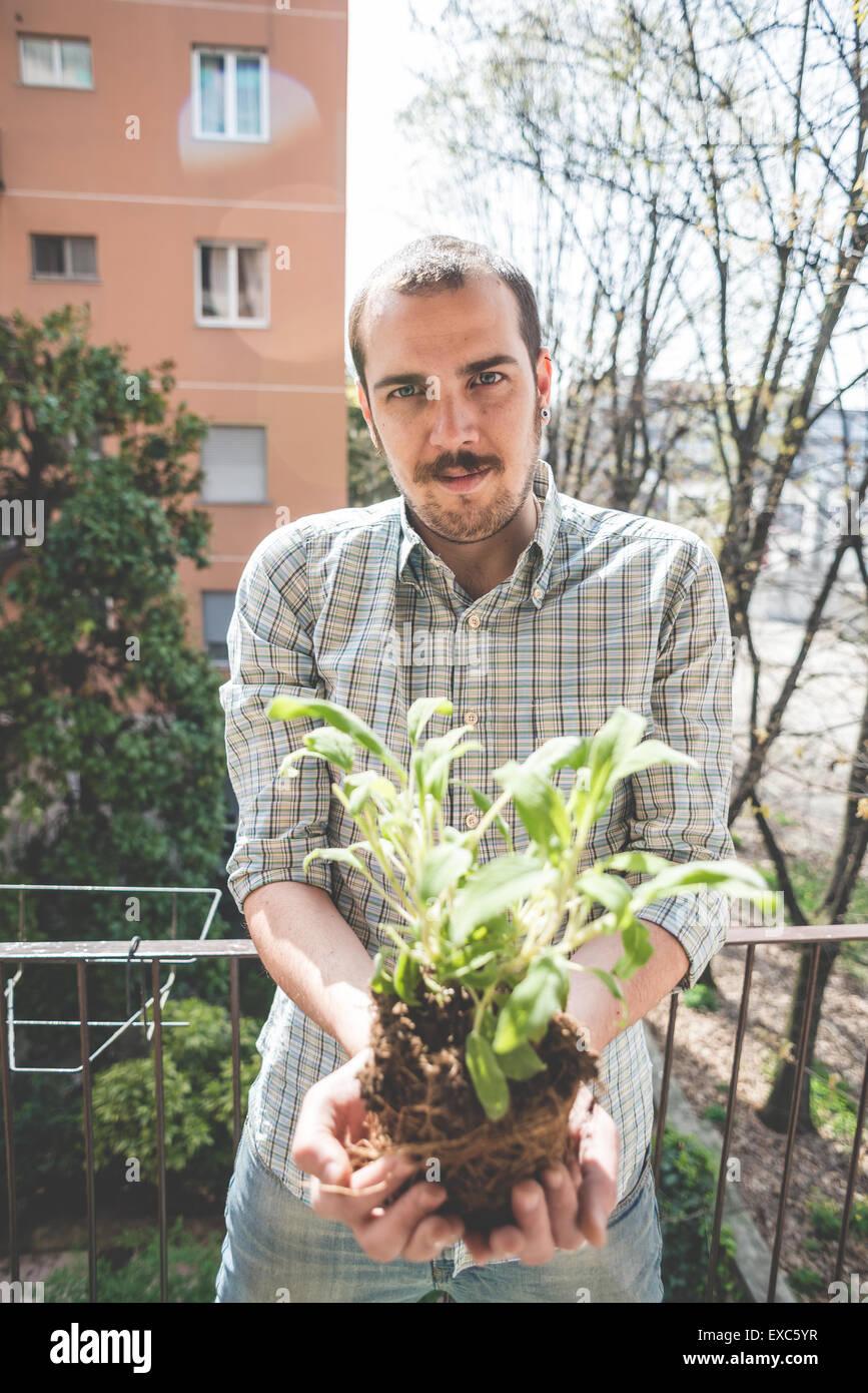 handsome stylish man holding basil plant at home Stock Photo