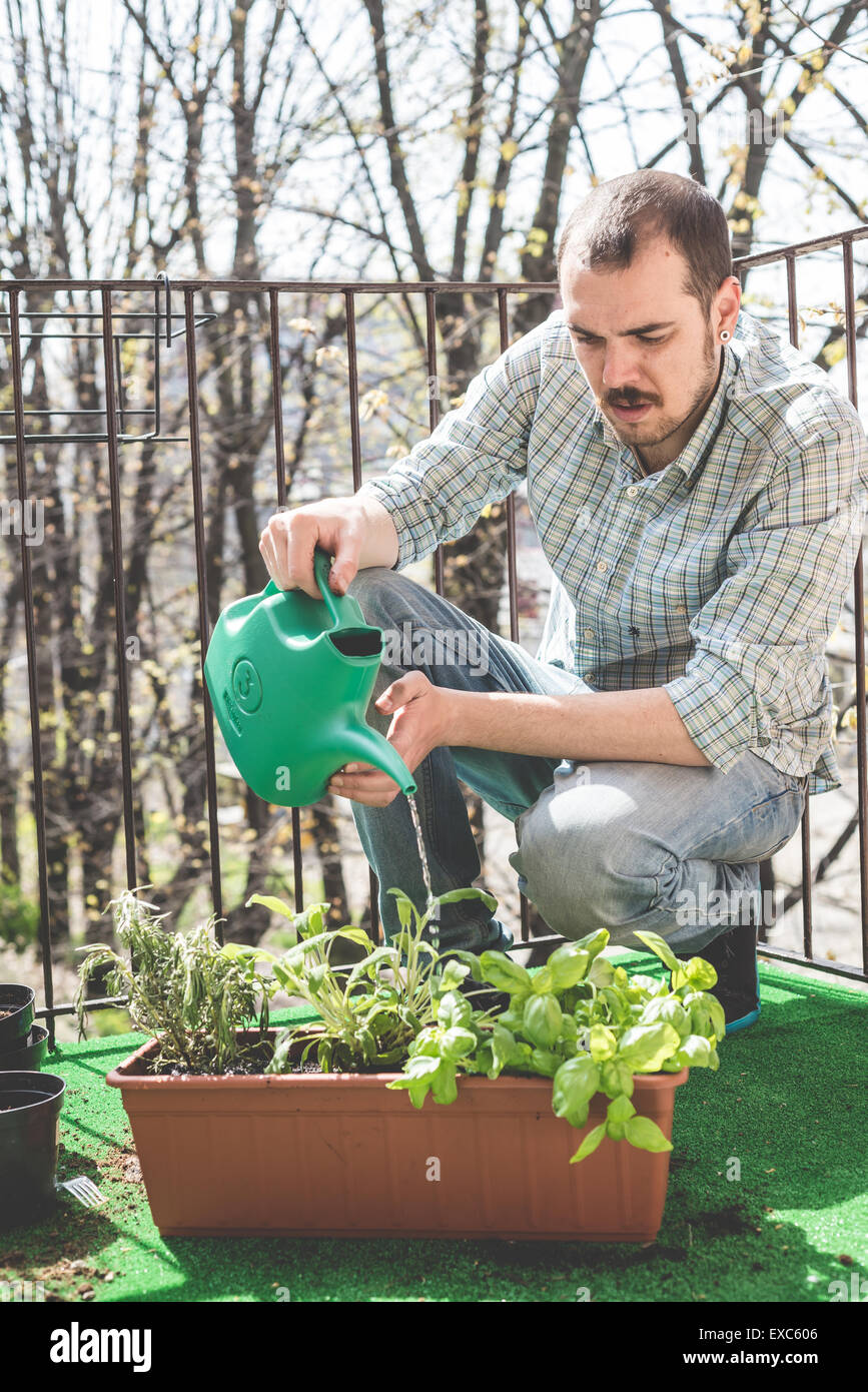handsome stylish man gardening and watering at home - Stock Image
