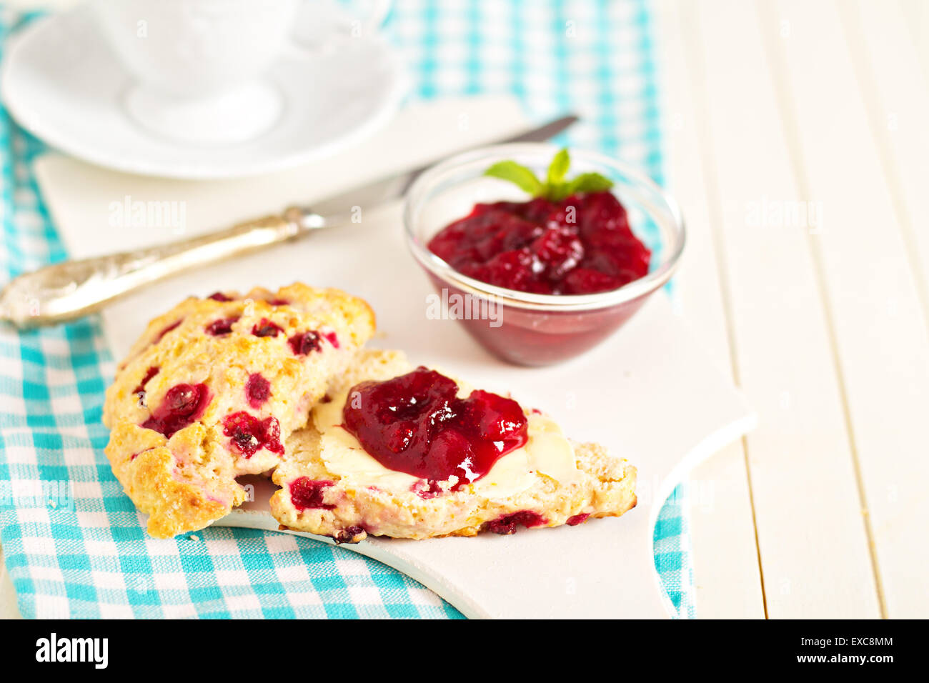 Scone with orange zest and berries with butter and jam - Stock Image