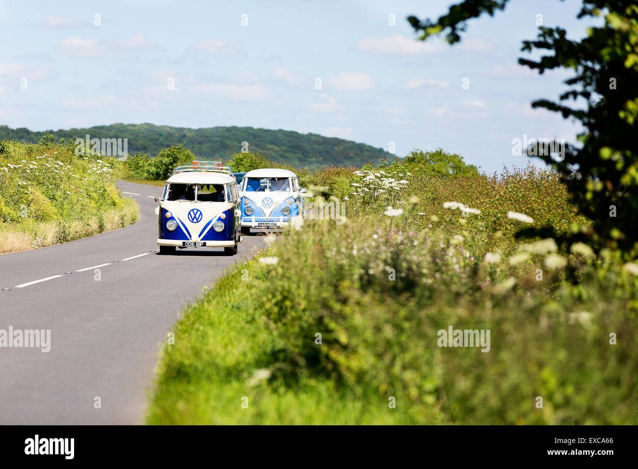 Two old classic 1960's VW Camper vans driving through the english summer country side countryside in convoy - Stock Image