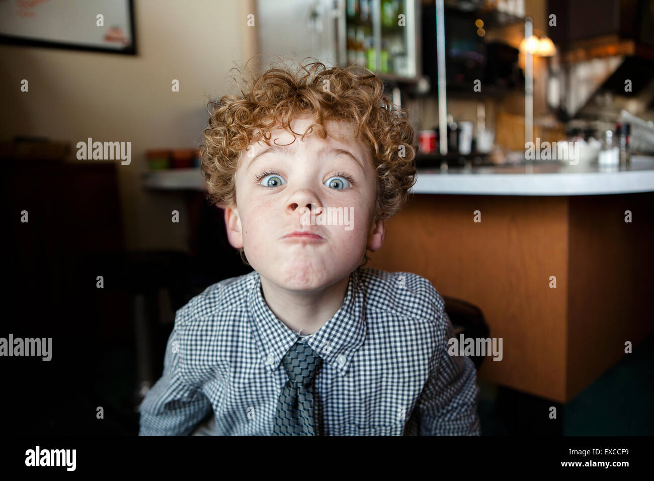A 6 year old boy wearing a dress shirt and tie making a goofy face - Stock Image