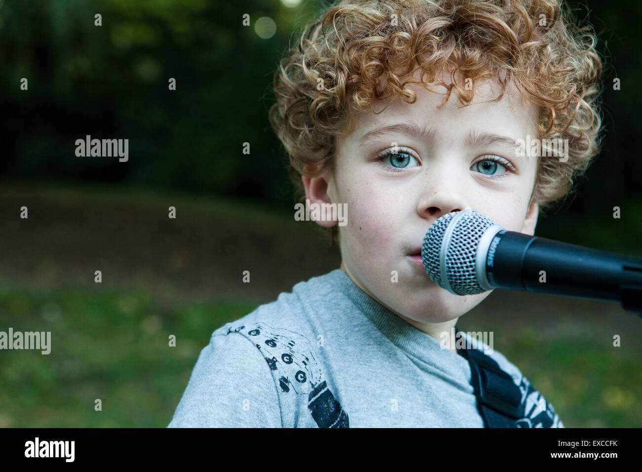 A young boy with curly red hair sings into a microphone. - Stock Image