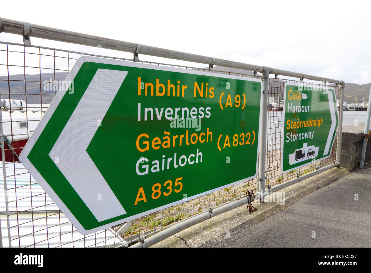 UK road directions signs in Ullapool, Scottish Highlands, promoting Gaelic over English - Stock Image