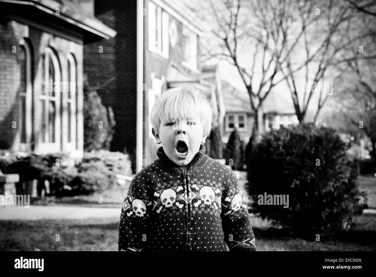 A crabby young blond boy wearing a sweater with skulls stands in the front yard of a house in a neighborhood. Stock Photo