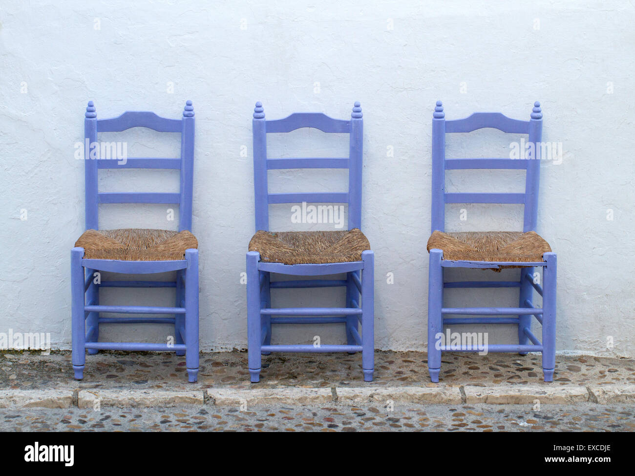 Old Blue Wooden Chairs Alone In The Mediterranean Street On A White Wall