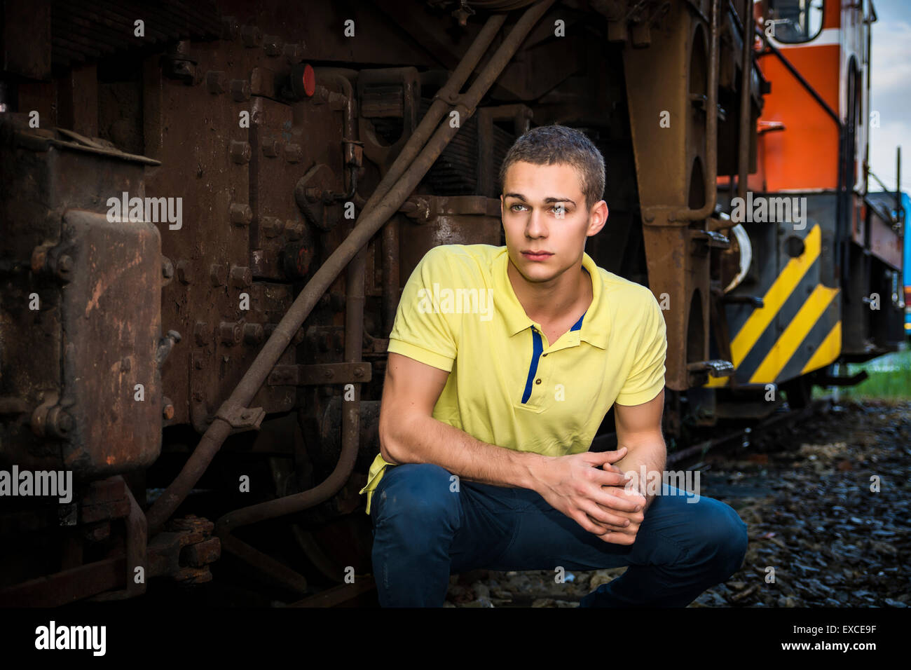 Handsome young man leaning against wood planks wall outdoor and looking at camera - Stock Image