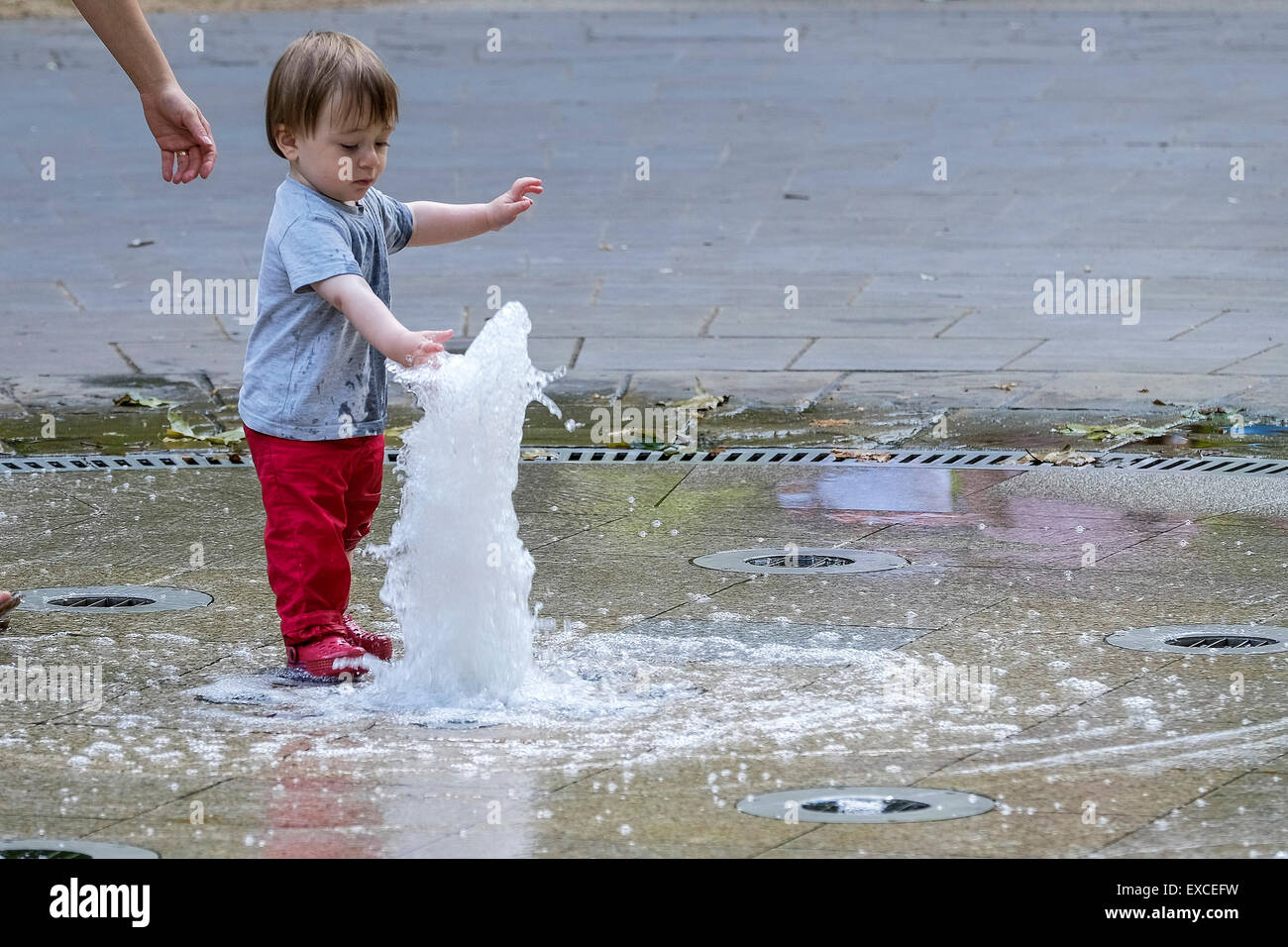 Russell Square Gardens, London, UK. 11th July, 2015.    A toddler escapes the heat in London today by cooling off - Stock Image