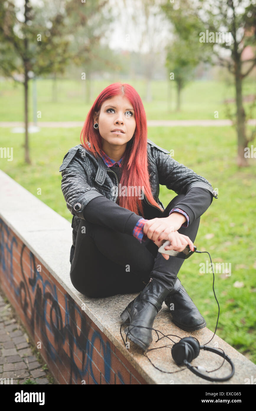 young beautiful red hair venezuelan woman lifestyle in the city of milan outdoor street listening music with headphones - Stock Image