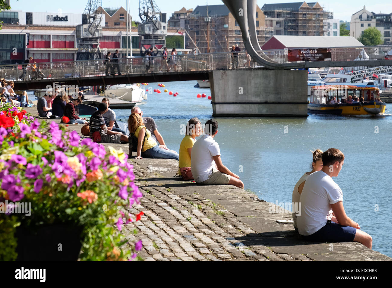 People relaxing and enjoying the sunshine at the Harbourside in Bristol, UK - Stock Image