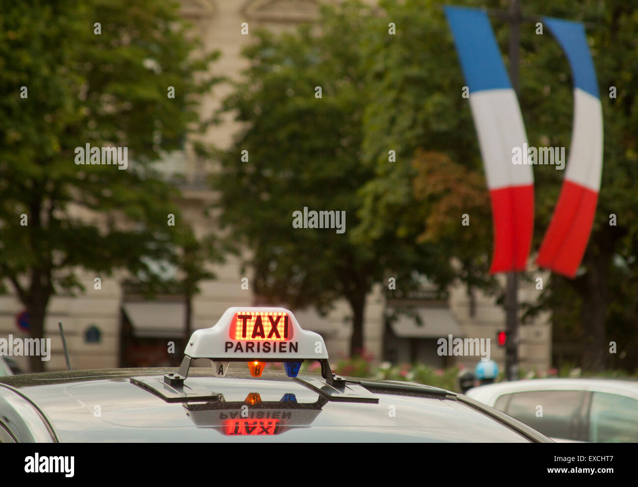 Taxi sign and its reflection on a roof of a taxicab with flags of France in background in Paris, France - Stock Image