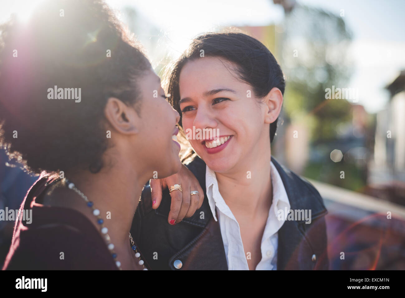 two multiethnic beautiful young woman black and caucasian having fun in town - Stock Image