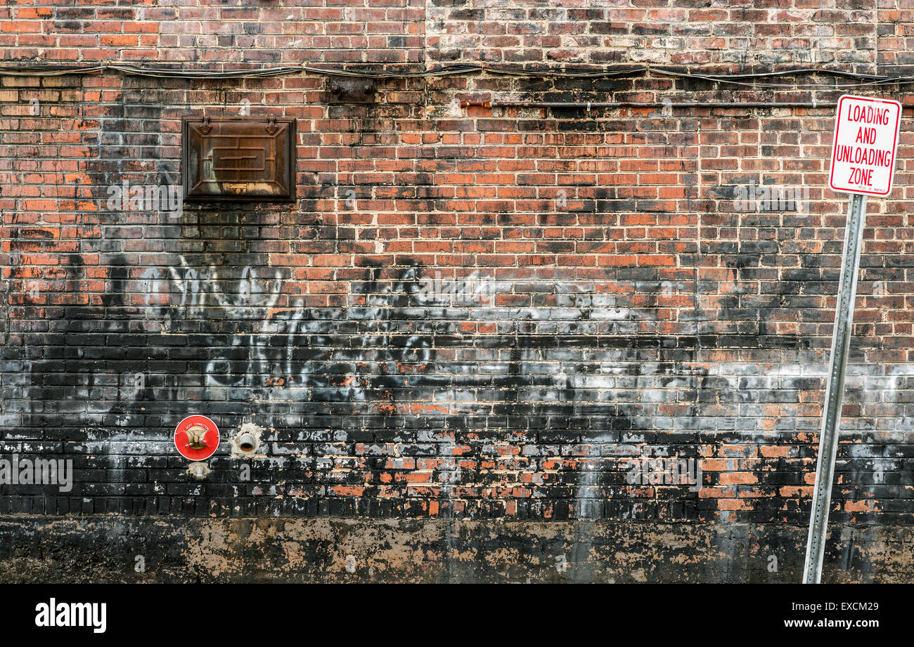 Grungy Urban Background Of Brick Wall With Graffiti - Stock Image