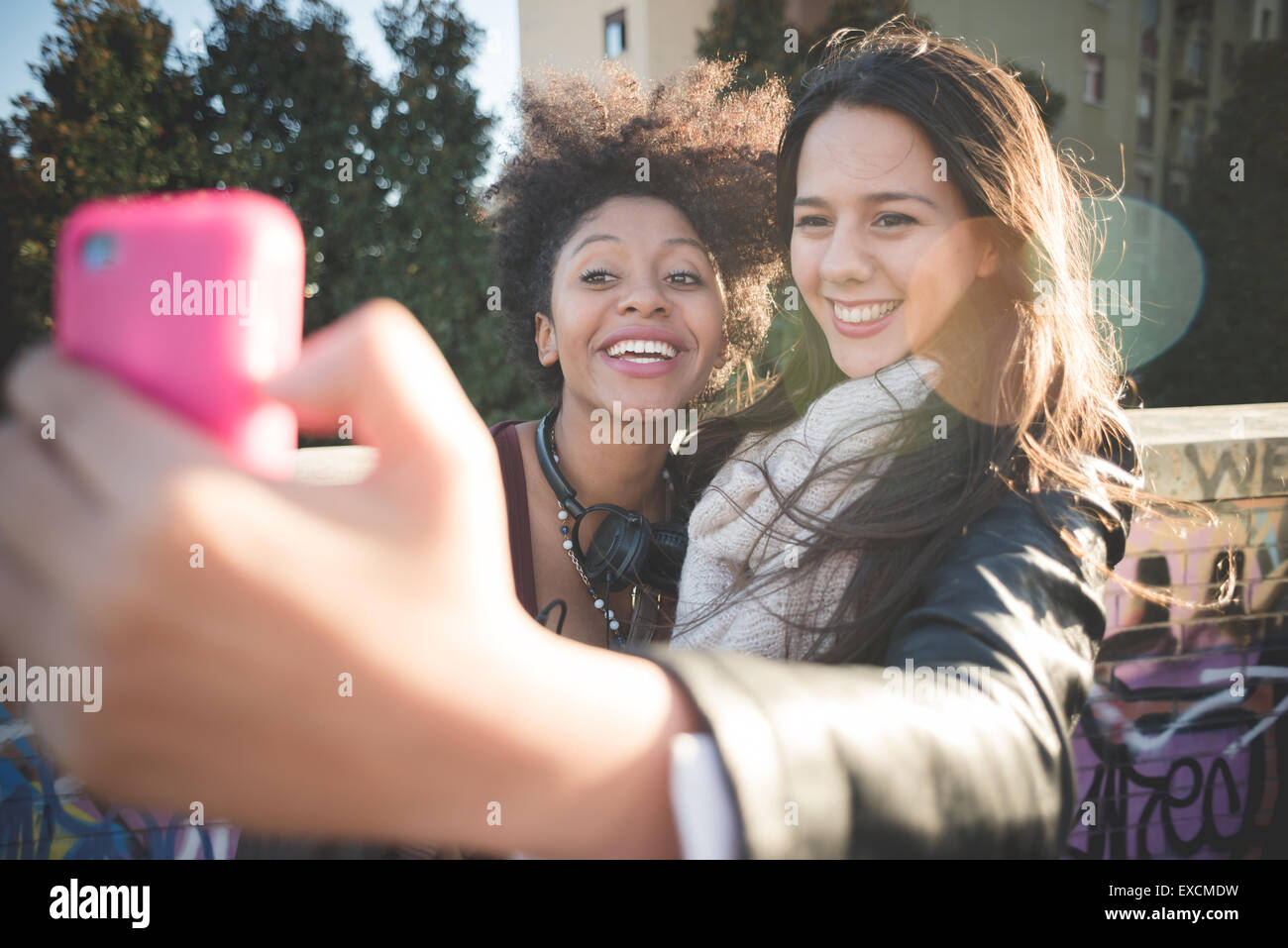 two multiethnic beautiful young woman black and caucasian having fun taking selfie in town - Stock Image