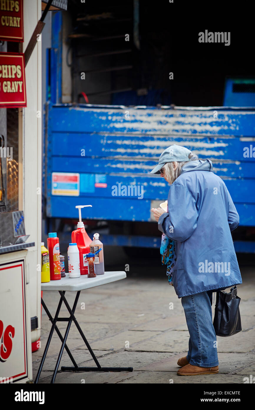 A lady buys a snack from a take-away on Liverpool Road in Manchester city centre   Snack fish chips burger food - Stock Image