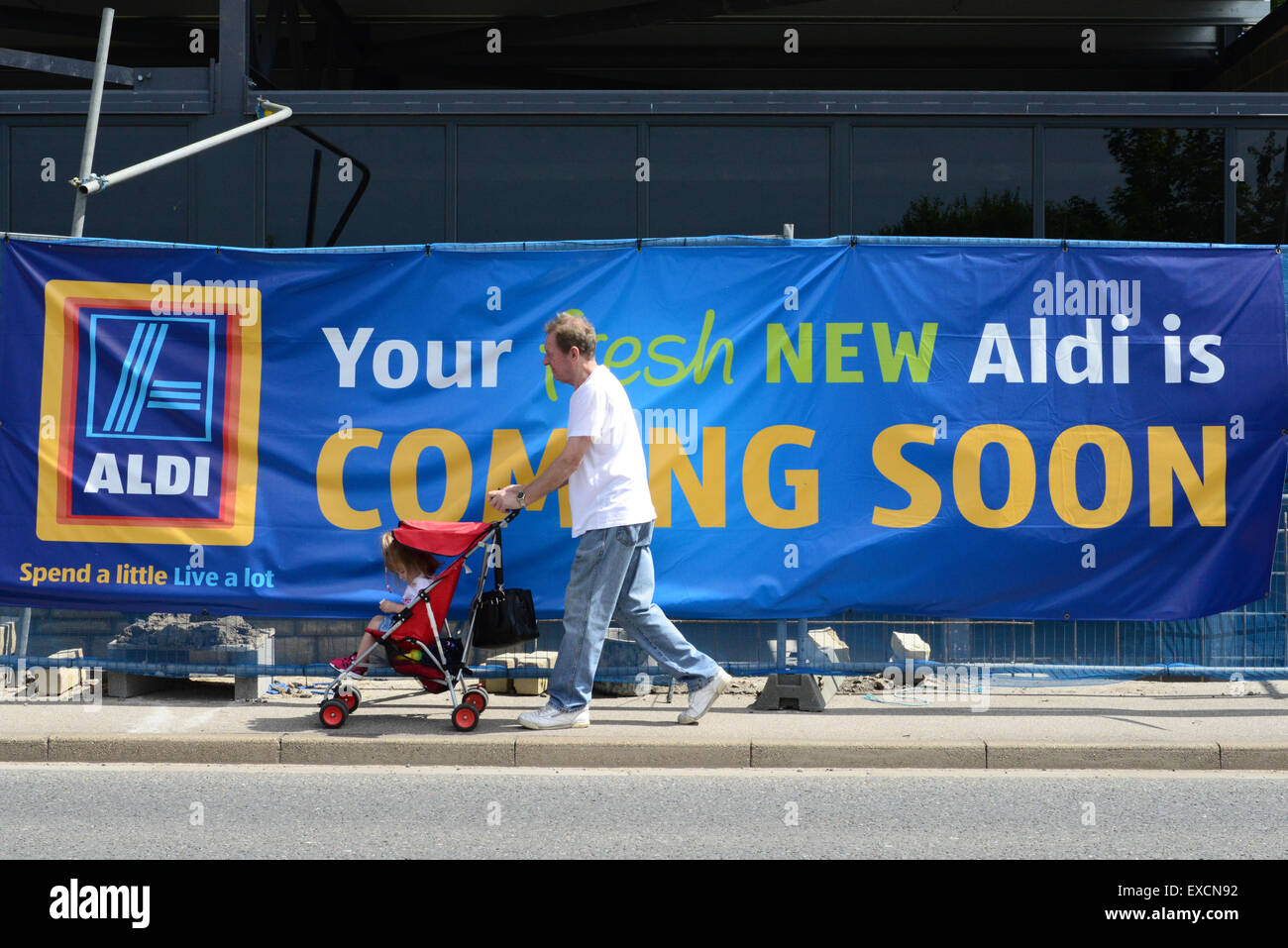 A man pushing a baby in a pushchair walks past a new Aldi Supermarket being built. Picture: Scott Bairstow/Alamy Stock Photo