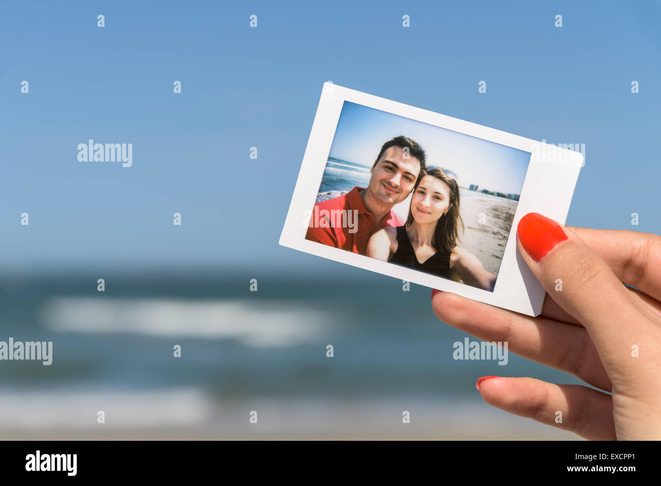 Girl Holding Instant Photo Of Young Happy Couple Stock Photo