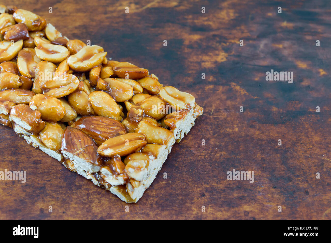 Honey bar with peanuts almonds and hazelnuts on a brown wooden board - Stock Image