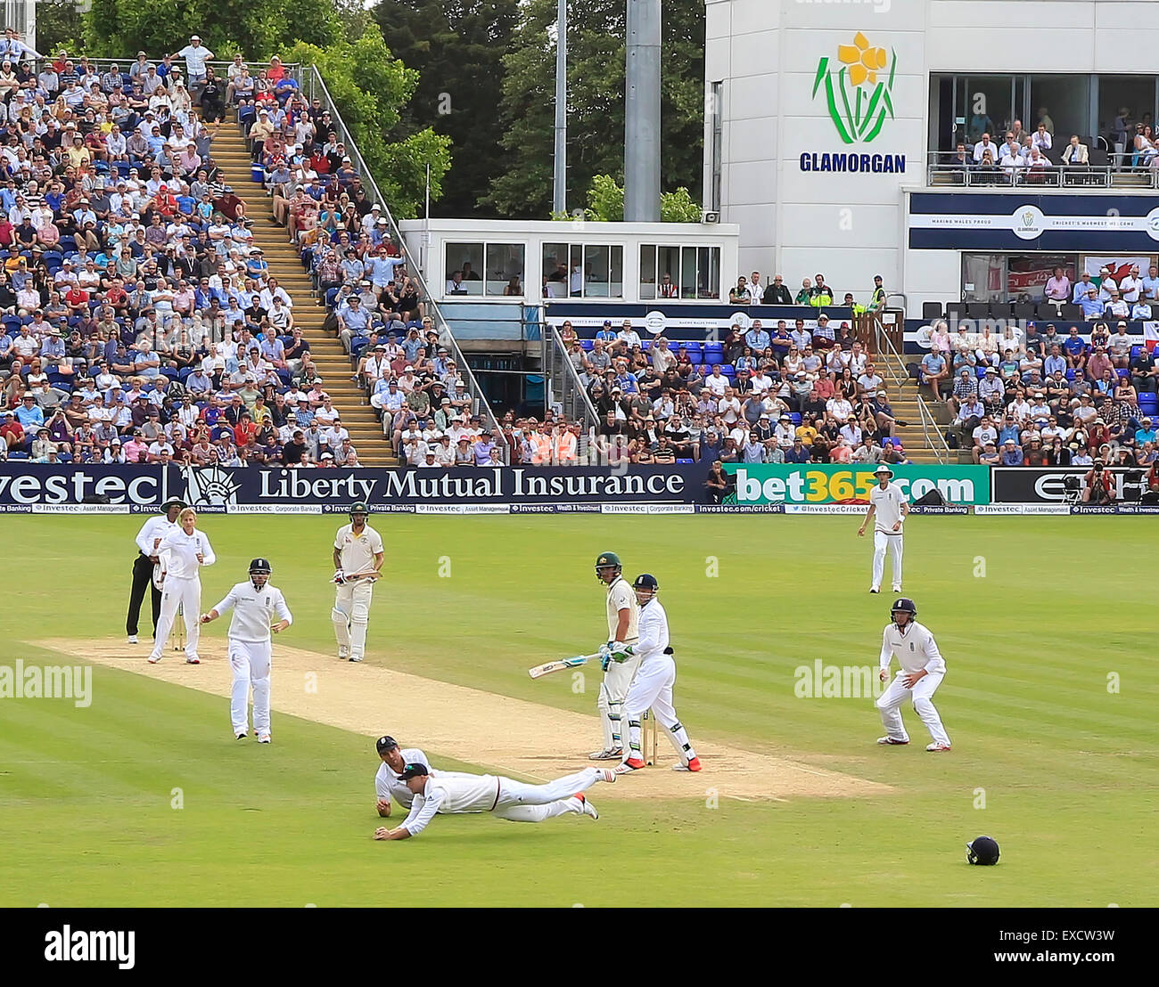 Cardiff, Wales, UK. 11th July, 2015. Joe Root and Alastair Cook look on as Adam Lyth catches the ball to dismiss - Stock Image