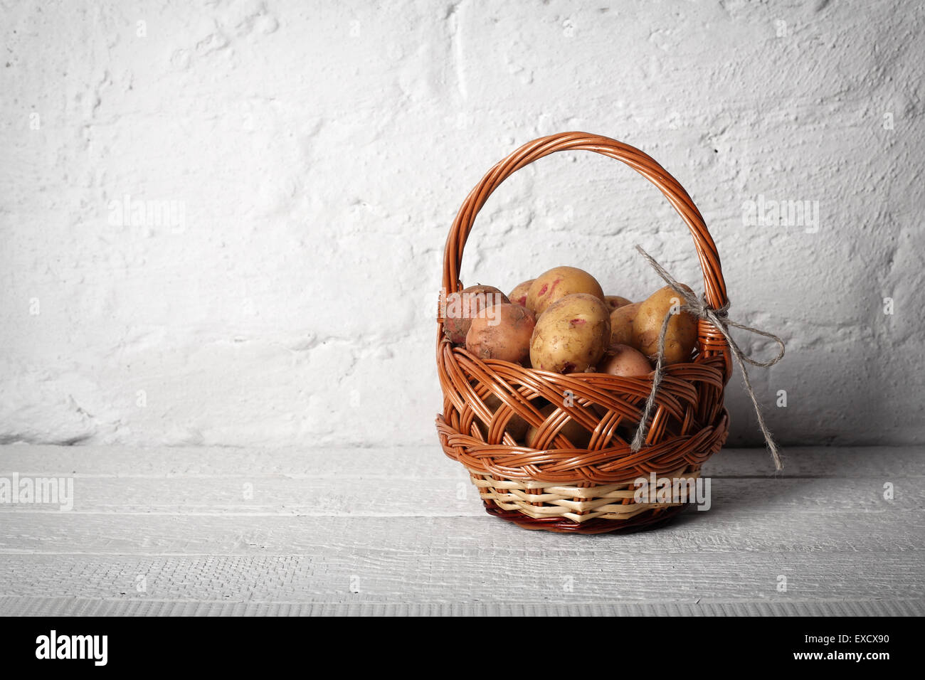 Basket with potatoes on old white planks a background - Stock Image