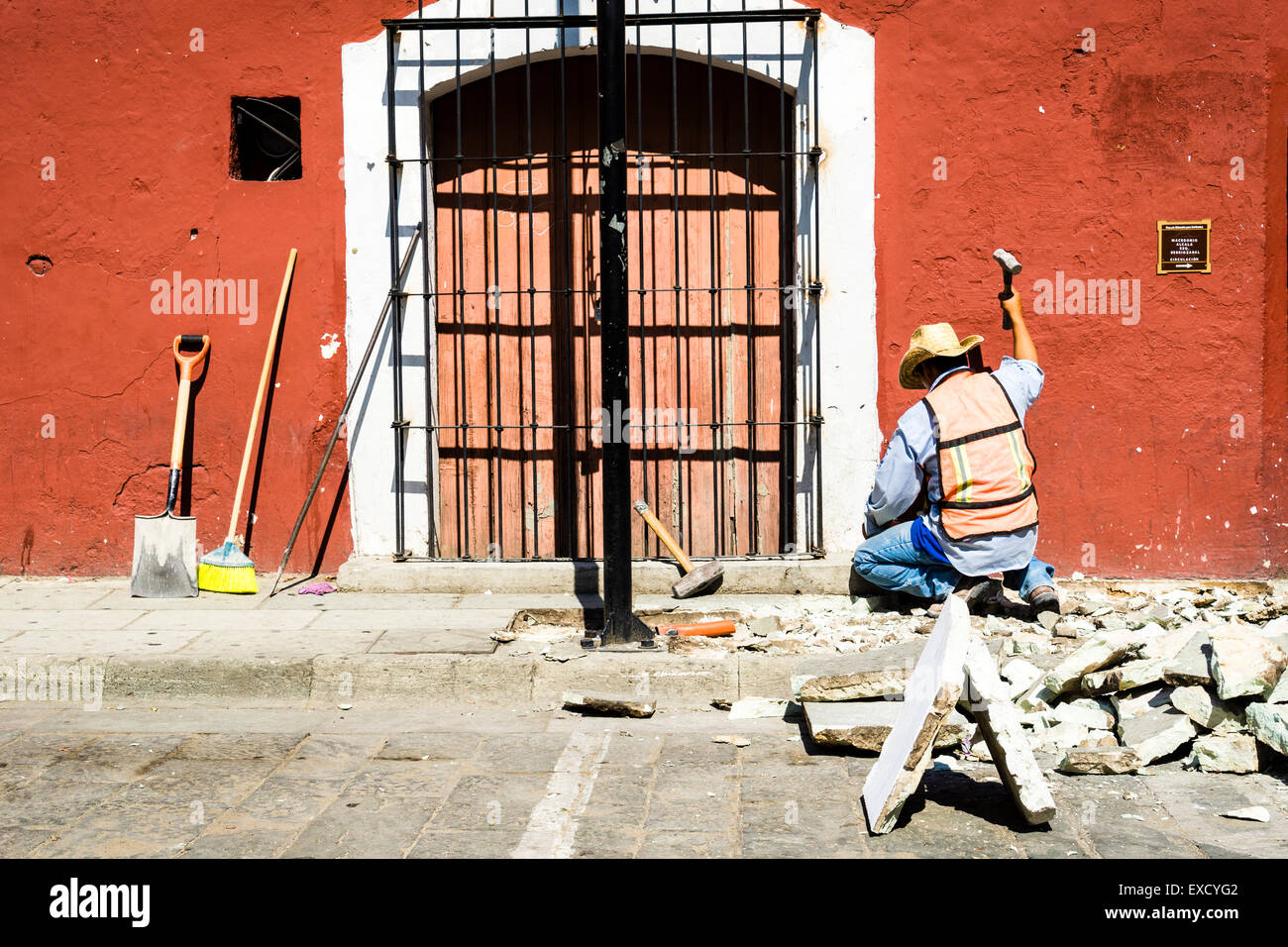 Construction worker swinging a hammer to tear up and repair stone sidewalk in the hot afternoon sun - Stock Image