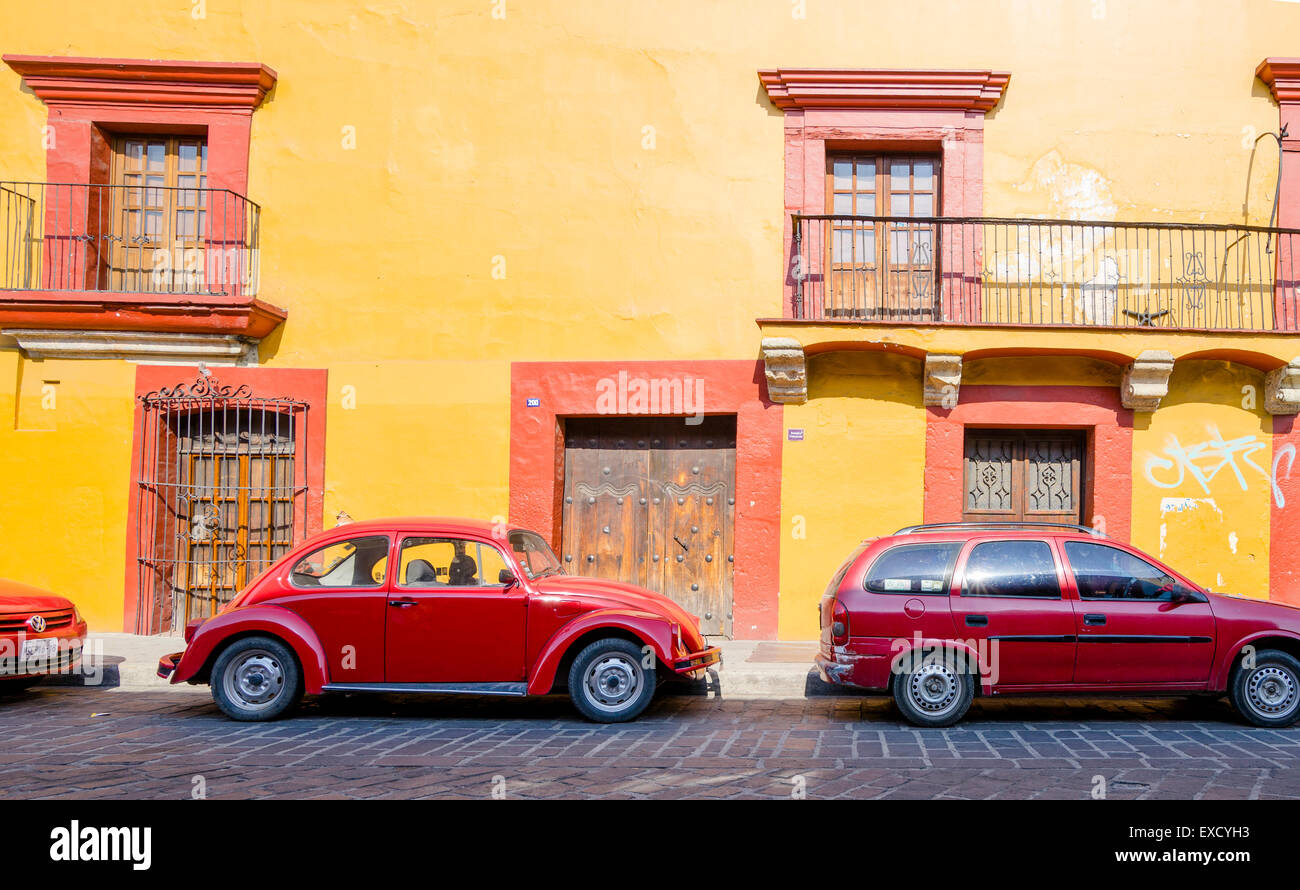 Bright red cars matching bright red and yellow building with misaligned doors and windows in historic downtown Oaxaca - Stock Image