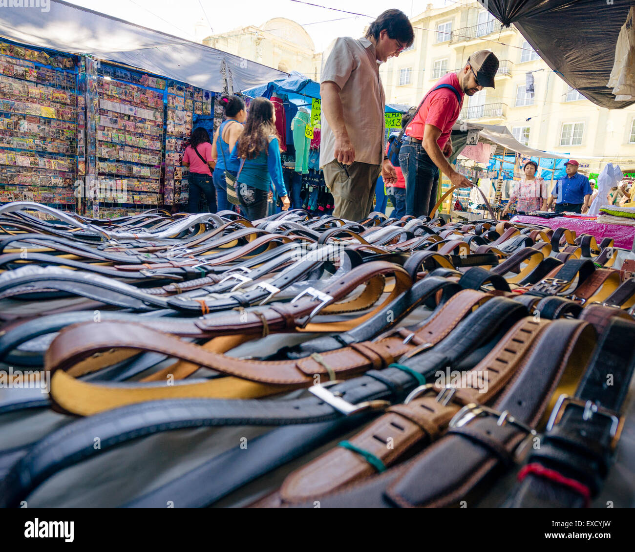 Men shopping for leather belts at the Zocalo market in Oaxaca Mexico - Stock Image