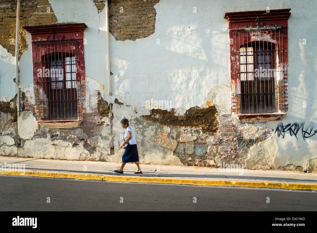 Woman walking up sloped street in front of old decaying stucco building facade - Stock Image