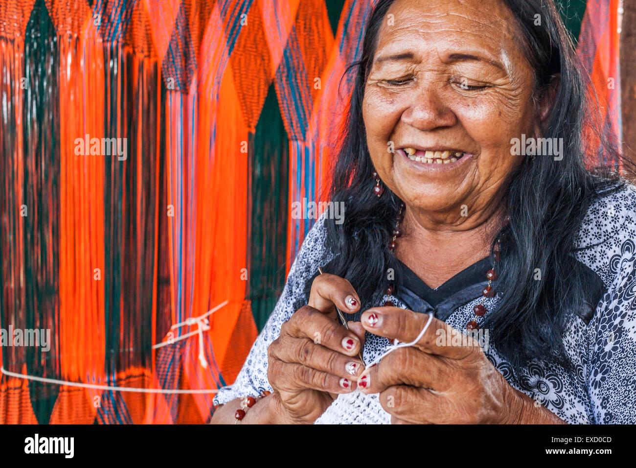 Elderly Wayuu indigenous woman weaving a 'chinchorro' or Colombian Hammock.  Knitting, crocheting and weaving - Stock Image