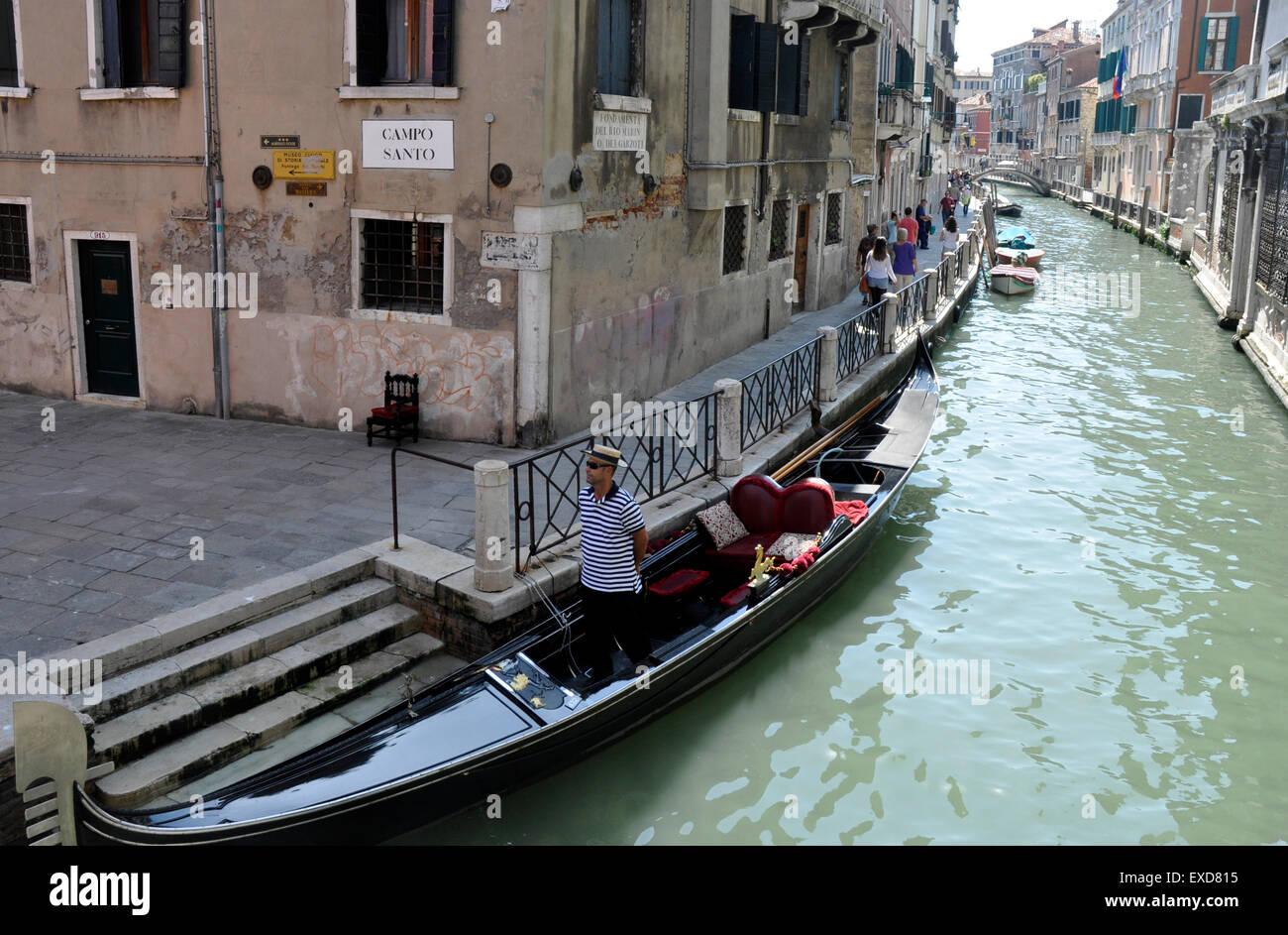 Italy Venice Cannaregio region canal at Campo Santo off Strada Nova - gondolier touting for tourists - sunlight - Stock Image