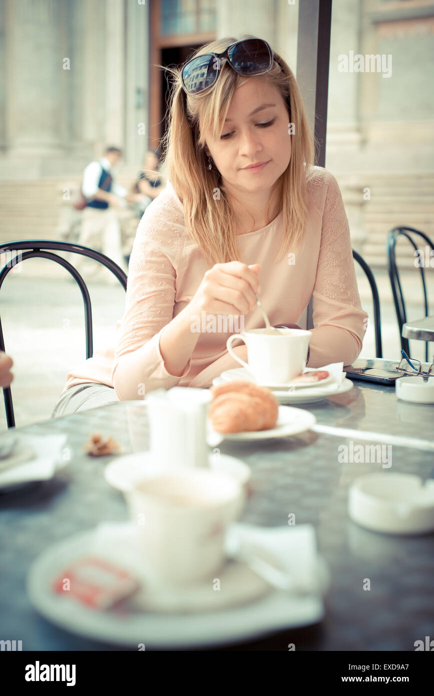 beautiful blonde woman having breakfast at the bar in the city Stock Photo