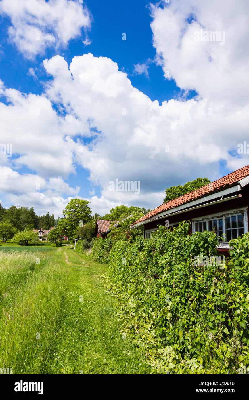 View of an Old Village in Sweden With a Blue Cloudy Sky - Stock Image