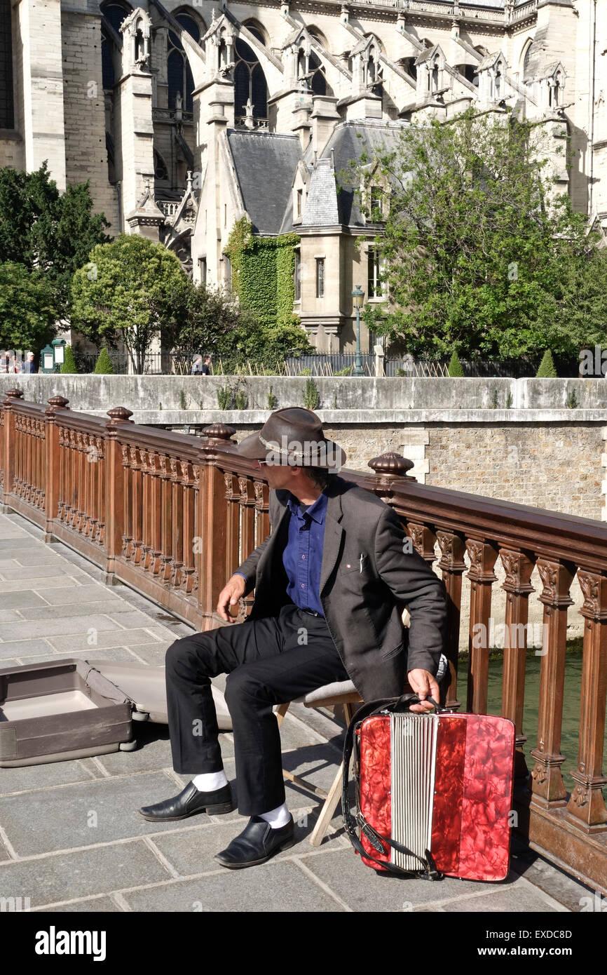 Accordion player at Pont au double, Notre-Dame Cathedral in fourth arrondissement, Ile de la Cite, Paris. France. - Stock Image