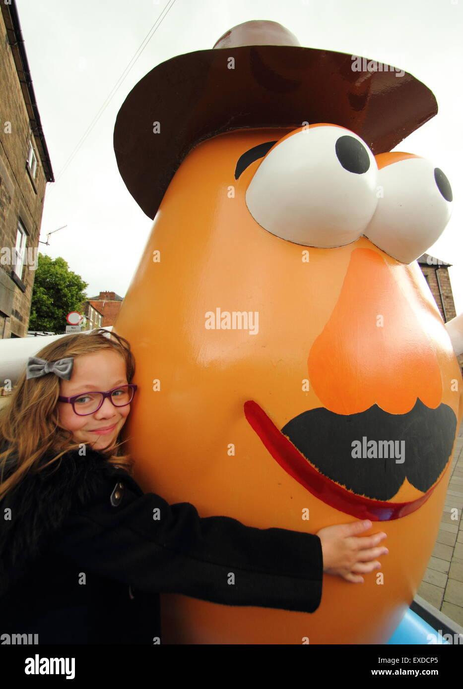 Belper, Derbyshire, UK. 12th July, 2015. Brii Matheson, 8,from Belper hugs a giant Mr Potato Head that has re-appeared - Stock Image